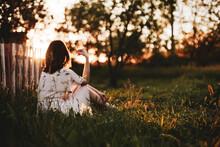 Girl Sit Back In Village Background At Sunset