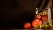 Ripe Pumpkins, Apples And Pears In Wooden Box On Dark Brown Background With Copy Space. Thanksgiving Background. Autumn Harvest