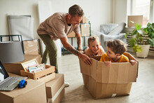 Portrait Of Modern Father Playing With Two Boys In Cardboard Box While Family Moving To New House, Copy Space