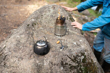Rest In The Countryside In Nature. Camping. A Fire In A Woodchip And A Kettle, Flint. A Man In A Blue Clothes On Background