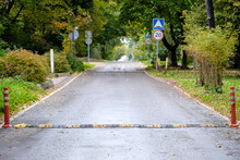 Asphalt Road Receding Into The Distance In The Suburbs. Traffic Safety Speed Bump In The Foreground. Selective Focus