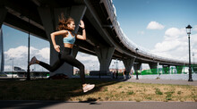 The Athlete Leads A Healthy Lifestyle. Cardio Training For Weight Loss. Sports And Clothing For Women. Fitness In The City. A Professional Trainer Does Warm-up Exercises Before Training.