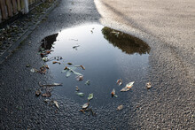 Large Puddle Caused By An Overflowing Soaraway Drain After A Heavy Downpour. The Textured Private Road Can Be Seen.