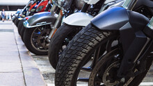 Motorcycles Parked On The Motorcycles Parking Lot On The Street. Closeup View Of Motorcycles Front Wheels