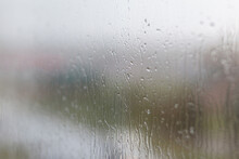 Rainy Day Through The Window On Cloudy Grey Sky And City Buildings Background. Concept. Evening Cityscape Behind The Glass Window With Trickling Drops Of Water.