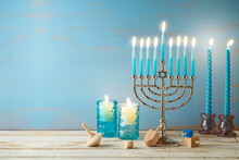 Jewish Holiday Hanukkah Concept With Menorah, Candles And Dreidel On Wooden Table. Background For Greeting Card Or Banner
