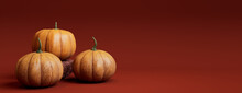 Seasonal Background Banner With Copy-space. Trio Of Pumpkins On Burnt Orange Color. Fall Concept.