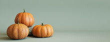 Three Pumpkins On A Grey Green Colored Background. Autumn Themed Banner With Copy-space.