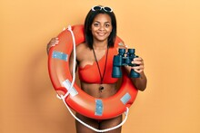 Young African American Girl Holding Lifeguard Floater Using Binoculars Smiling With A Happy And Cool Smile On Face. Showing Teeth.