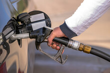MALE HAND HOLDING FUEL DISPENSER NOZZLE AND REFILLING A CAR IN THE GAS STATION.