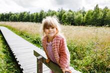 Little Girl Walking On Wooden Path On Black Moor Nature Landscape. Active Preschool Child Exploring National Park With Trees, Plants, Boggy Landscape.