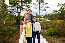 Little Girl, Two School Boys And Father Walking On Wooden Path On Black Moor Nature Landscape. Active Family With Three Children Exploring National Park With Trees, Plants, Boggy Landscape.