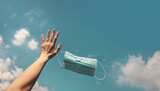 Fototapeta Kawa jest smaczna - Hope, Positive Mind for Coronavirus Concept. Hand Raised Up a Smiling Medical Mask into the Blue Sky. Gesture means Goodbye. Deep Breathing for Fresh Air