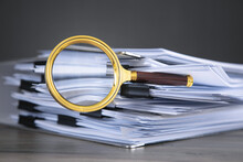 Stack Of Documents And Magnifying Glass On The Table.