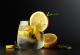 Fototapeta Kawa jest smaczna - Cocktail gin-tonic with lemon slices and twigs of rosemary on a black background.