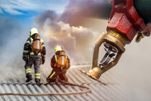 Sprinkler Close-up Near Firefighters. Firefighters On Roof Of Building. Firefighters Officers Fight Flames. Sprinkler Extinguishing Fire Close-up. Sprinkler As Symbol Preventive Fire Safety Measures