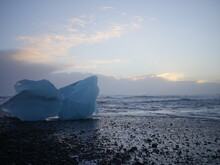 Pure Blue Ice Bergs In Iceland Washed Ashore By Sea Waves. Background Is A Sunset Pastel Colored Sky With Cloud.