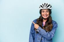 Young Caucasian Woman Rinding A Bike Isolated On Blue Background Smiling And Pointing Aside, Showing Something At Blank Space.