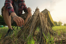 Selective Focus, Bonfire With Biomass Wood Material For Campfire. A Man Tourist Making Bonfire And Set Camping Tent. Survival Concept.