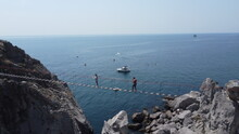 Two People Walk The Cableway To The Diva Rock Off The Coast Of The City Of Simeiz In Crimea.