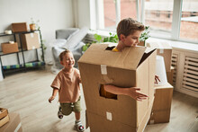 Portrait Of Two Brothers Wearing Cardboard Boxes And Playing While Family Moving To New House, Copy Space