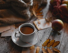A Cup Of Coffee On A Wooden Background, Apples In A Bag Are On The Table.