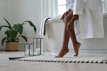 Young Black African Woman Wearing Bathrobe Touching Legs Soft Smooth Skin Applying Lotion Doing Body Care Morning Routine In Bathroom. Spa, Laser Epilation Hair Removal, Depilation. Close Up