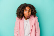 Young African American Woman With Curly Hair Isolated On Blue Background Shrugs Shoulders And Open Eyes Confused.