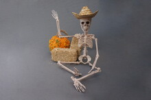 White Skeleton With Straw Hat Two Balses Of Hay And Orange And Green Popcorn Pumpkin On Gray Background