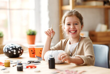Cute Little Girl Smiling, Holding Paintbrush And Painting Halloween Pumpkin  At Home