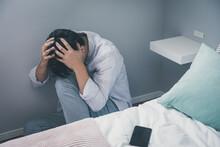 ベッド脇で頭を抱える男性  頭を抱える人  落ち込む男性