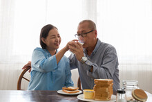 Asian Elderly Couple Having Bread Breakfast And Drinking Milk With Carefully In The Kitchen Room At Home