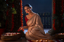 Indian Gorgeous Woman Posing In Front Of Camera With Flowers In Hand While Decorating Entrance On Diwali