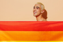 Side View Young Smiling Blond Latin Gay Man With Make Up In Beige Tank Shirt Hiding With Rainbow Flag Look Aside Isolated On Plain Light Ocher Background Studio Portrait People Lgbt Lifestyle Concept.
