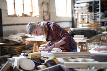 Portrait Of Female Carpenter With Goggles Working On Her Product Indoors In Carpentry Workshop. Small Business Concept.