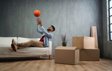 Happy Young Man With Basketball Celebrating Moving Home Surrounded By Packing Boxes, New Living Concept.