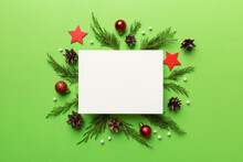 Flat Lay Christmas Composition. Square Paper Blank, Pine Tree Branches, Christmas Decorations On Colored Background. Top View, Copy Space For Text