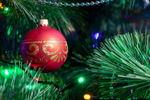 Christmas Decoration, Red Glass Ball On A Green Christmas Tree Branch. Christmas Garland On Tree. Shallow Depth Of Field Ball With Golden Ornament. New Year Background With Soft Focus