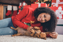 Photo Of Sweet Adorable Dark Skin Lady Wear Red Pullover Smiling Petting Puppy Lying Floor Carpet Indoors Room Home House