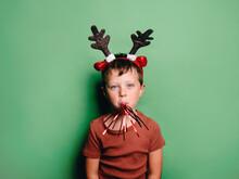 Boy In Deer Antlers Headband Blowing Noisemaker