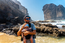 A Young Father With His Baby In His Backpack In The Roque Del Moro Of The Cofete Beach Of The Natural Park Of Jandia, Barlovento, South Of Fuerteventura, Canary Islands. Spain