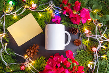 Christmas Background Minimalist Concept. Mug And Christmas Greeting Cards With Spruce Leaves, Fir Flowers, Paper Flowers (Bougainvillea) And Christmas Lights.