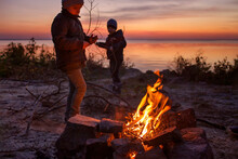 Kids Of Different Ages Sit Near Fire On Autumn Seashore After Sunset, Communicate And Have A Good Time Together, Trust And Friendship, Active Family Weekend. Autumn Outside Lifestyle. Focus On Fire