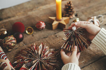 Stylish Handmade Angel From Festive Red Wrapping Paper In Hands On Background Of Rustic Wooden Table With Paper Stars, Candle. Atmospheric Moody Image. Merry Christmas ! Holidays Preparation