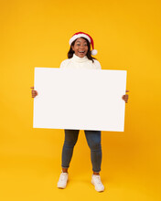 African Woman Showing Empty Poster Wearing Santa Hat, Yellow Background