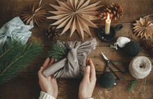 Christmas Gift Rustic Flat Lay. Hands Holding Stylish Xmas Gift Wrapped In Brown Fabric On Rustic Wooden Table With Scissors, Paper Star, Candle. Atmospheric Moody Image. Furoshiki Wrap, Zero Waste