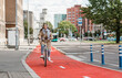 canvas print picture - traffic, city transport and people concept - happy smiling woman riding bicycle along red bike lane or two way road on street