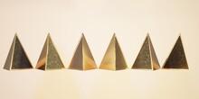 3D Illustration Of Several Golden Pyradmids For Background