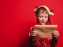 Child Reading Letter In Red Studio On Christmas Day