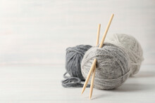 Balls Of Yarn With Knitting Needles On White Wooden Background